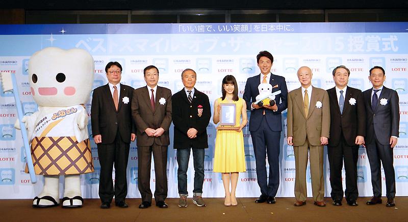 受賞した二人(中央)と浅井愼平審査委員長(左から3人目)を囲むベストスマイル実行委員会
