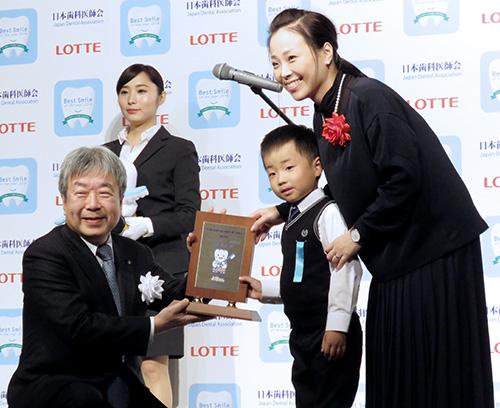 受賞者に記念品を手渡す日歯・堀憲郎会長